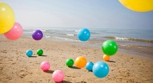 Colorful beach balls bouncing on sand